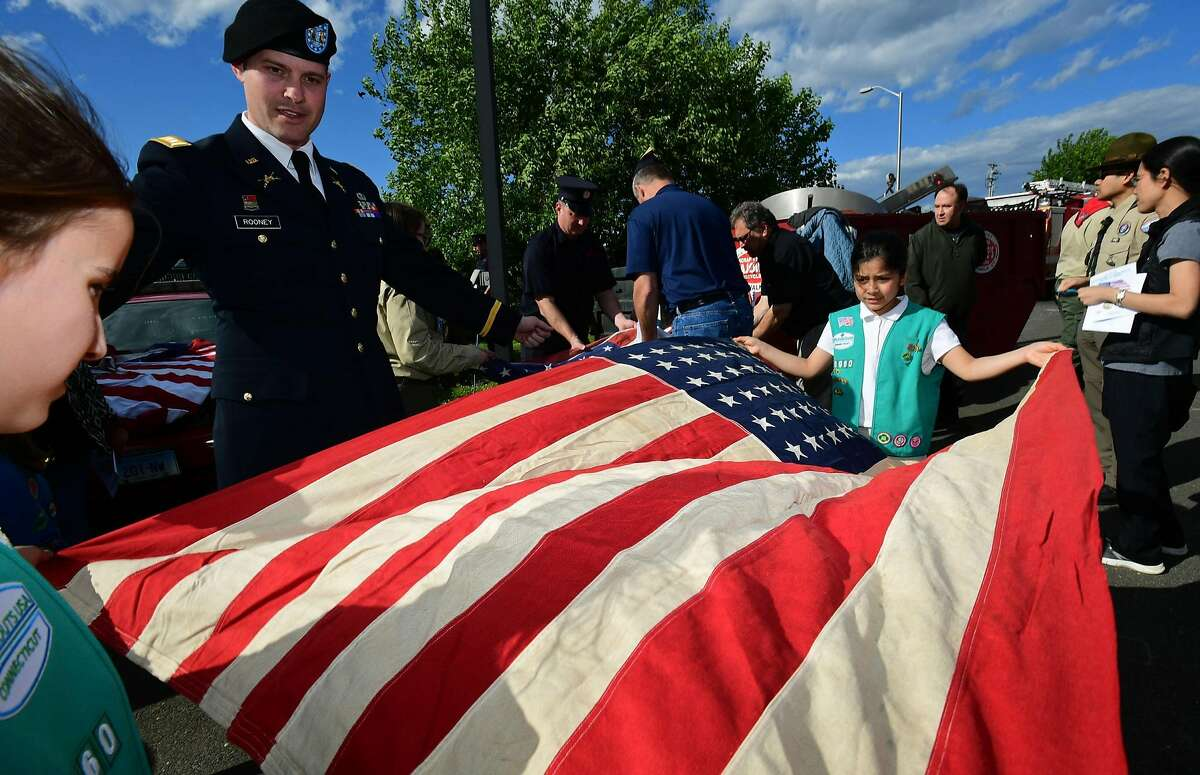 Army National Guard Captain Brian Rooney shows girl scouts, Christina Vlicky and Stephanie Rodriguez how to fold a flag as they take part in a ceremony on Flag Day to respectfully retire worn American flags that have been proudly flown over Norwalk, Friday, June 14, 2019, at the Norwalk Fire Department maintenance garage in Norwalk, Conn. The ceremony, organized by The American Legion Frank C. Godfrey Post 12, the Norwalk Fire Department and Scouts BSA Troop 19, invited all community organizations, interested citizens and Scout units to participate.