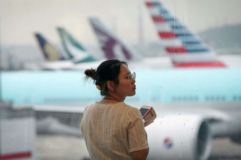 A woman reacts as airplanes are parked at the Hong Kong International Airport, Monday, Aug. 12, 2019. One of the world's busiest airports canceled all flights after thousands of Hong Kong pro-democracy protesters crowded into the main terminal Monday afternoon. Photo: Vincent Thian, AP / Copyright 2018 The Associated Press. All rights reserved
