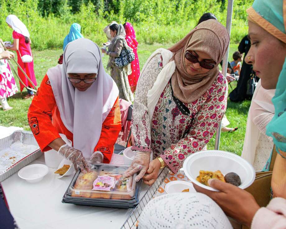 Carol Scott and Shabana Syeda hand out food during Eid ul Adha, a holiday to honor Abraham and Ishmael, at the Islamic Center of the Capital District in Colonie NY, on Sunday, Aug. 11 (Jim Franco/Special to the Times Union.) Photo: James Franco / 20047600A