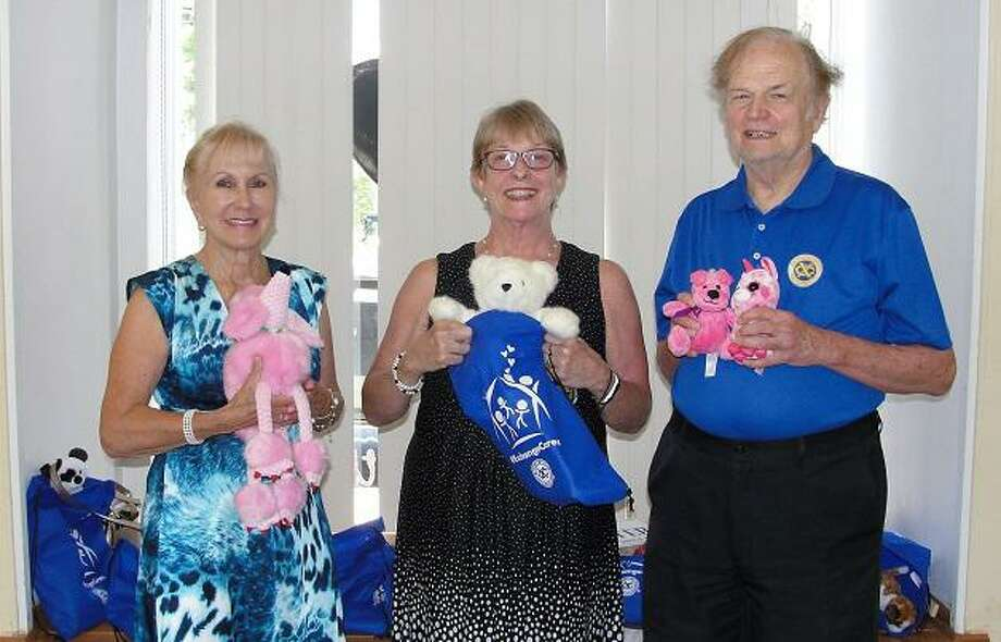 Nick Percival, president of the Exchange Club of Ridgefield (XCR), presents the club's gift of 18 tote bags to Pat Zachman, center, president and CEO of the Women's Center of Greater Danbury. Dyane MacDaniel-Brandt, a member Exchange Club of Ridgefield and current president emeritus of Ridgefield's Meals on Wheels, helps with the toting. Photo: Contributed Photo /