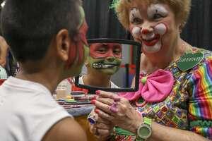 Greenie the Clown, Linda Greene, shows David Montez III his Mutant Ninja Turtle face paint during the Family Fun Day on Saturday, Aug. 10, 2019 at the Horseshoe Pavilion.