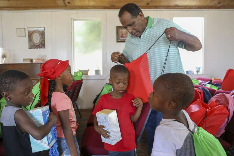 Pastor Dennis Hodges distributes free backpacks to children during Cops, Kids and Bar-B-Q was Saturday, Aug. 10, 2019 at Mount Moriah Disciples of Christ. Photo: Jacy Lewis/191 News