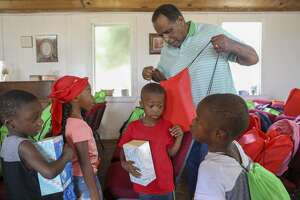 Pastor Dennis Hodges distributes free backpacks to children during Cops, Kids and Bar-B-Q was Saturday, Aug. 10, 2019 at Mount Moriah Disciples of Christ.