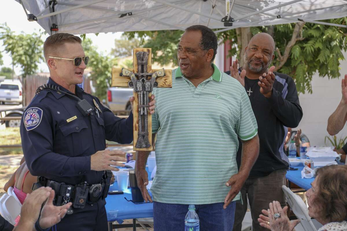 Pastor Dennis Hodges gives a cross to Midland Police Department Chief Seth Herman during Cops, Kids and Bar-B-Q was Saturday, Aug. 10, 2019 at Mount Moriah Disciples of Christ.