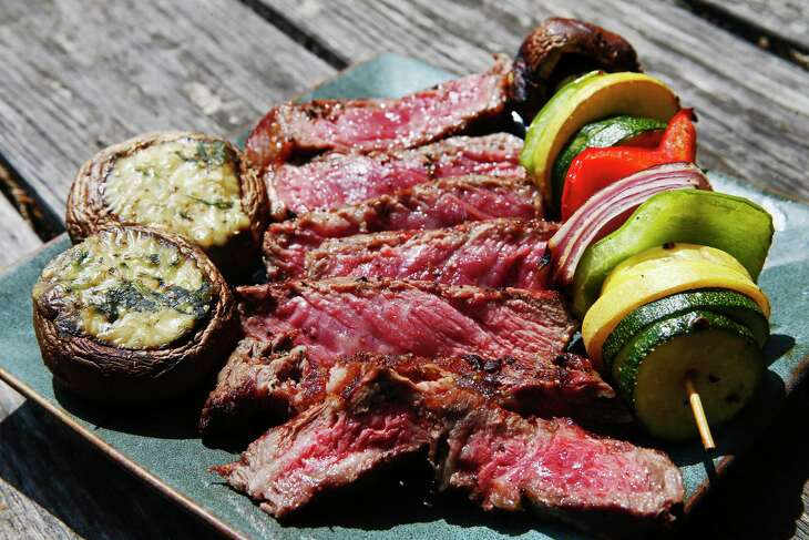 Sliced Wagyu rib-eye steak is plated with stuffed mushrooms and vegetable kabobs.