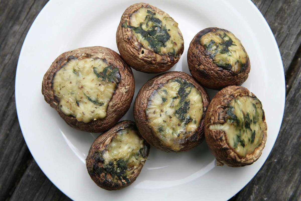 A finished dish of creamy spinach-stuffed mushrooms.
