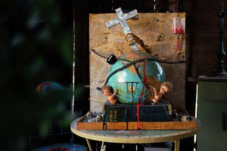 An art piece by Joey Piscitelli titled Clergy Abuse, Money, Power, Religion and Hell - On A Stack of Bibles, is seen at his home in Martinez, Calif., on Wednesday, July 31, 2019. Piscitelli's mixed media art piece depicts earth, religion and the catastrophic connection to abused children, money, power and hell.