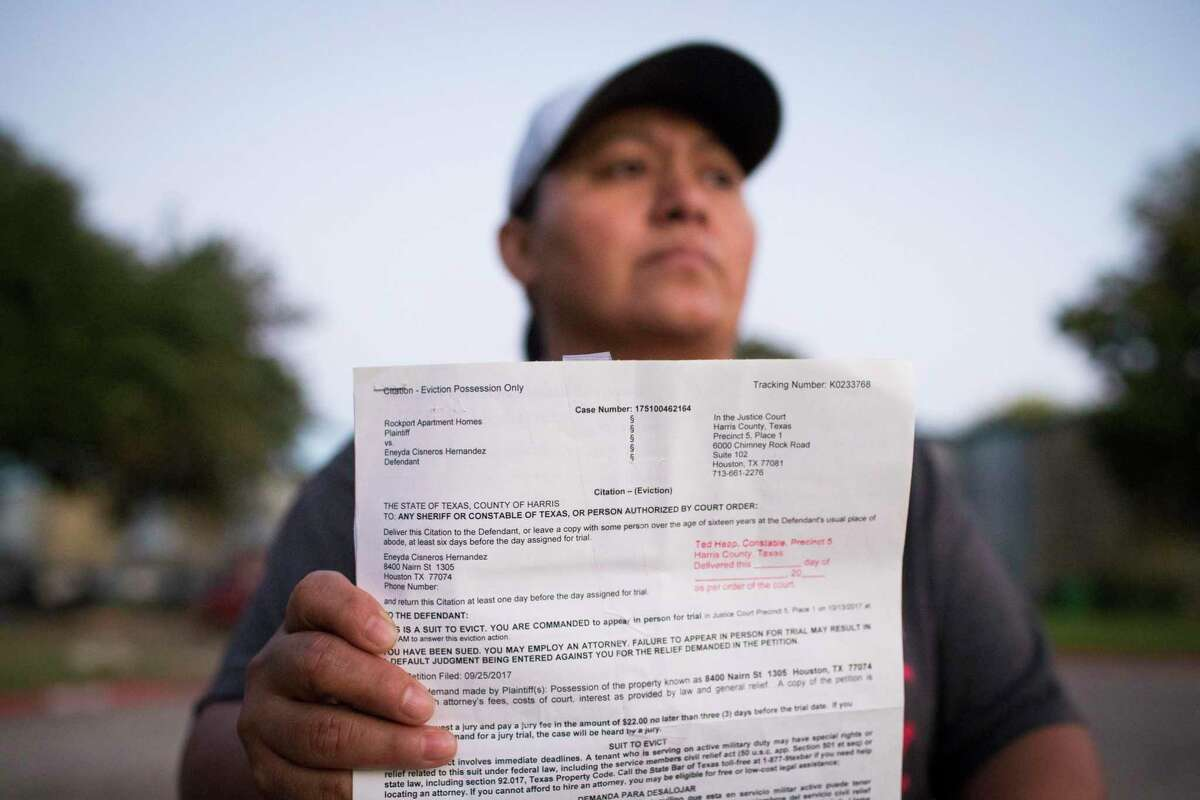 Eneyda Cisneros Hernandez holds an eviction citation she received from Rockport Apartment Homes, the complex where she lives in Houston, Sunday, Oct. 22, 2017.