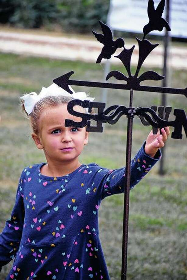 Three-year-old Ella Biedermann of Washington, who was in Illinois visiting her grandparents, plays with a hummingbird weather vane during Sunday's Hummingbird Festival. Photo: David Blanchette | For The Telegraph