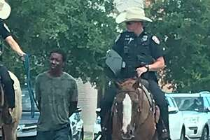 In this photo provided by Erin Toberman, Donald Neely, center, is walked with handcuffs and a rope by two mounted police officers in Galveston, Texas, on Saturday, Aug. 3, 2019. Galveston's police chief has apologized for the way Neely was treated. (Courtesy of Erin Toberman via AP)