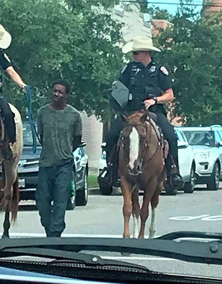 In this photo provided by Erin Toberman, Donald Neely, center, is walked with handcuffs and a rope by two mounted police officers in Galveston, Texas, on Saturday, Aug. 3, 2019. Galveston's police chief has apologized for the way Neely was treated. >> Keep clicking through the following gallery to see recent racist and controversial incidents in Houston and the rest of Texas. Photo: Associated Press / Erin Toberman via the Family