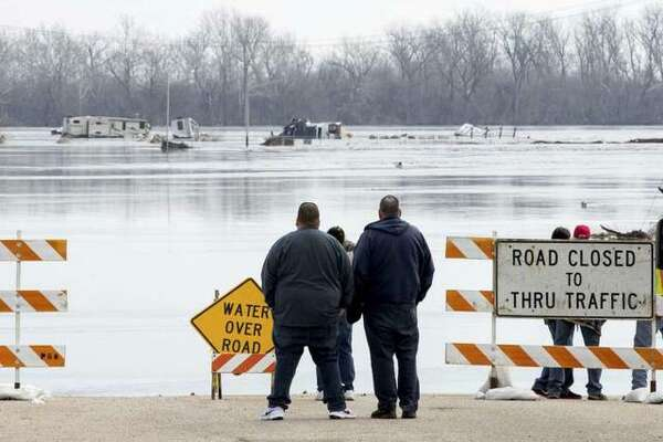 In this March 17, 2019 file photo, people stand at the edge of a flooded road in Plattsmouth, Neb. Although President Donald Trump has expressed doubt about climate change, even calling it a hoax, a National Climate Assessment released last year by the White House warned that natural disasters in the U.S. are worsening because of global warming.