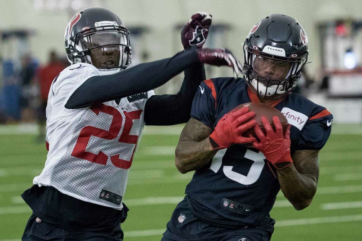 Houston Texans wide receiver Tyron Johnson (13) hauls in a reception with defensive back Deante Burton (25) defending during training camp at the Houston Methodist Training Center on Monday, Aug. 12, 2019, in Houston.