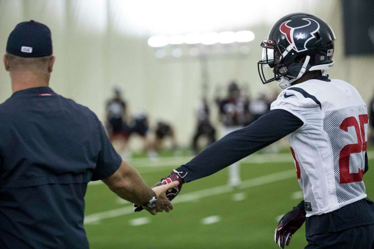 Houston Texans head coach Bill O'Brien slaps hands with defensive back Deante Burton (25) during training camp at the Houston Methodist Training Center on Monday, Aug. 12, 2019, in Houston.