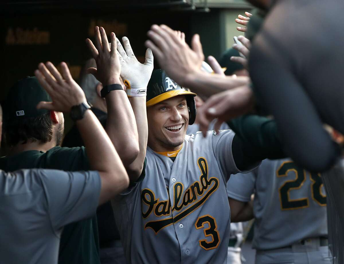 Oakland Athletics' Dustin Garneau celebrates in the dugout after hitting a three-run home run off Chicago Cubs starting pitcher Jon Lester during the second inning of a baseball game Tuesday, Aug. 6, 2019, in Chicago. (AP Photo/Charles Rex Arbogast)