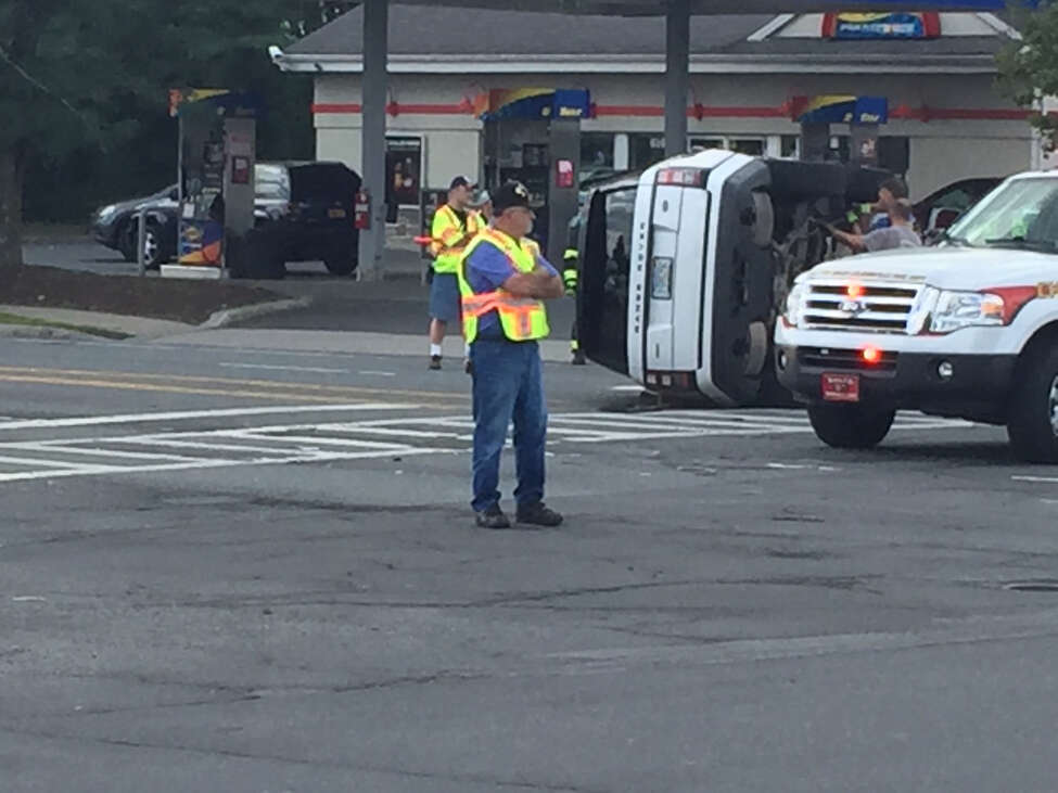 A fire official directs traffic after an SUV rolled in the intersection of Wolf Road and Albany Shaker Road in Colonie.