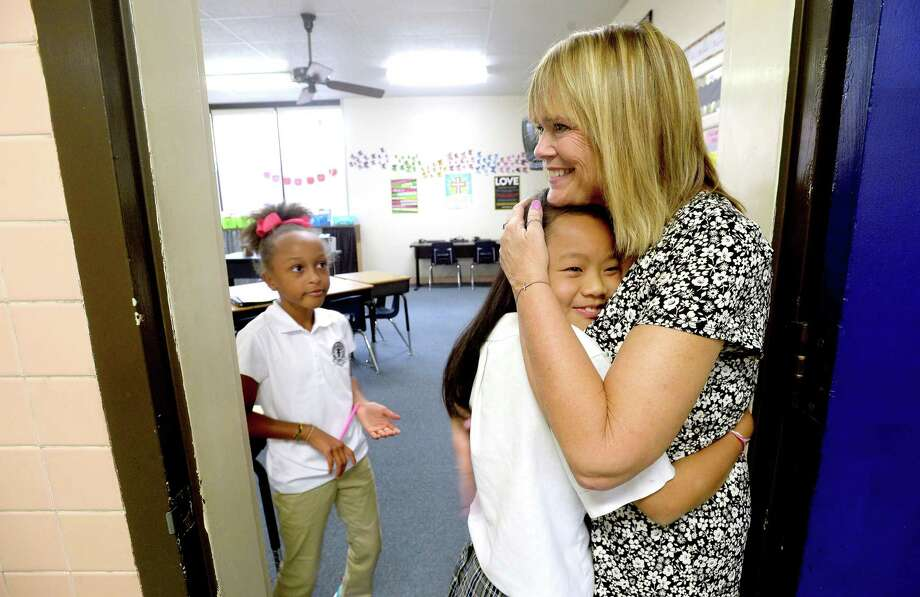 Fourth-grader Avery Redmon looks on as Kirstyna Dal hugs their third grade teacher Laura Smith at the end of the first school day at St. Anthony Cathedral Basilica School in Beaumont. The first day of school for many public school students throughout the region begins mid-week. 