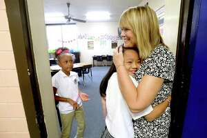 Fourth-grader Avery Redmon looks on as Kirstyna Dal hugs their third grade teacher Laura Smith at the end of the first school day at St. Anthony Cathedral Basilica School in Beaumont. The first day of school for many public school students throughout the region begins mid-week.  Photo taken Monday, August 12, 2019 Kim Brent/The Enterprise
