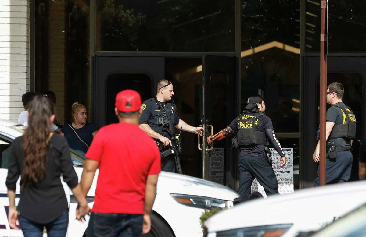In this Sunday, Aug. 11, 2019, photo, people stand outside Memorial City Mall in Houston, as police investigate a disturbance causing an evacuation of the shopping center. Hundreds of panicked people rushed out of the Texas mall after a masked man jumped on a food court table and said he would kill himself before throwing down an unknown object covered in toilet paper. (Brett Coomer/Houston Chronicle via AP)