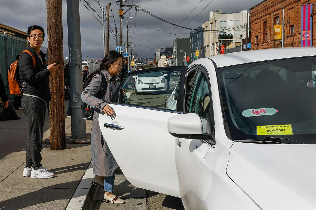 A woman gets into a Lyft car outside the Cal Train station on Townsend Street in San Francisco, California, on Monday, May 20, 2019. Both Uber and Lyft have agreed to a 3.25%-per ride tax in an effort to avoid a tax on their gross receipts. The taxes will generate an estimated $30 million to $35 million for transportation improvements and street-safety upgrades.