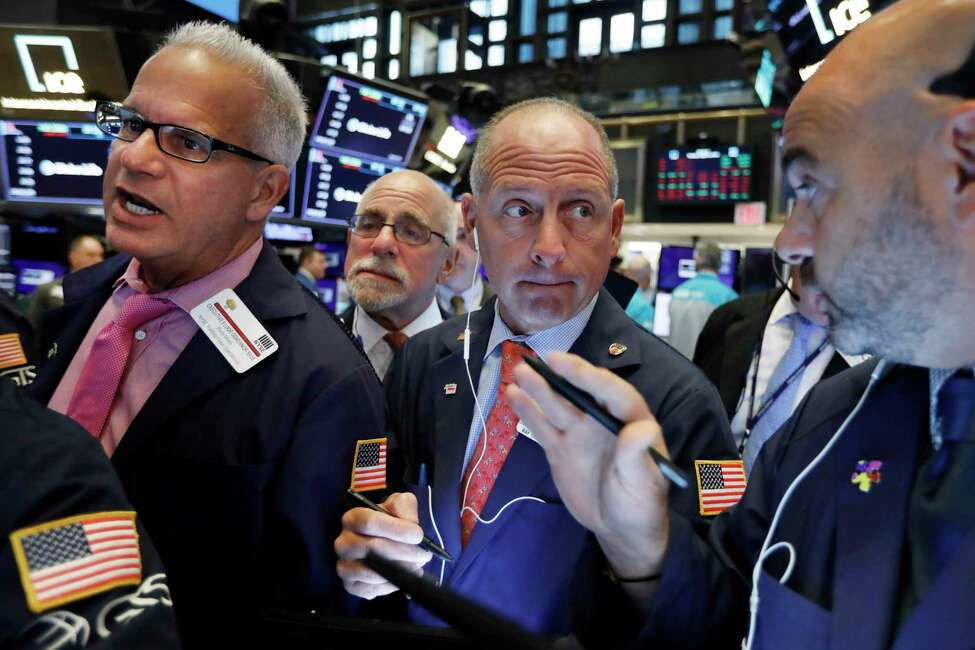 Michael Urkonis, second from right, works with fellow traders on the floor of the New York Stock Exchange, Monday, Aug. 12, 2019. Stocks are edging lower in early trading on Wall Street amid investor concerns that the U.S.-China trade war may be worsening. (AP Photo/Richard Drew)