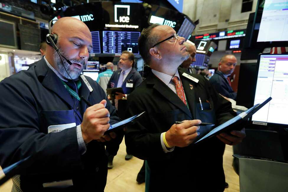 Traders Vincent Napolitano, left, and Robert Arciero work on the floor of the New York Stock Exchange, Monday, Aug. 12, 2019. Stocks are edging lower in early trading on Wall Street amid investor concerns that the U.S.-China trade war may be worsening. (AP Photo/Richard Drew)