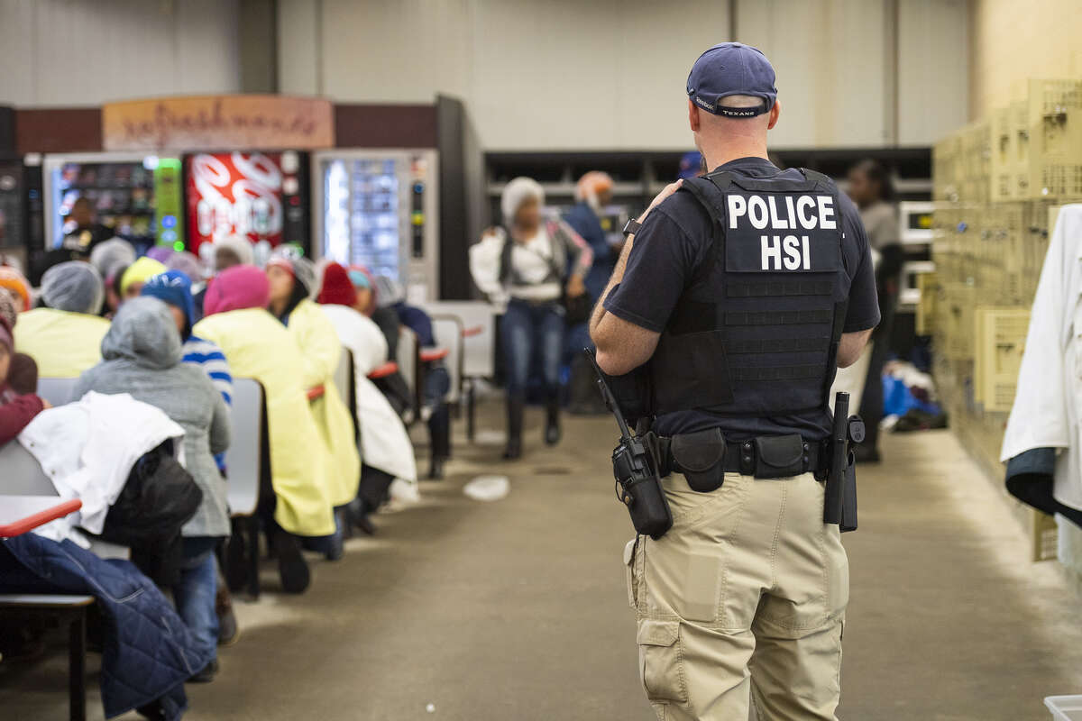 This image released by the US Immigration and Customs Enforcement (ICE) shows a Homeland Security Investigations (HSI) officer guarding suspected illegal aliens on August 7, 2019. Officers detained approximately 680 aliens who were unlawfully working at at seven agricultural processing plants across Mississippi. - US officials said that some 680 undocumented migrants were detained in a major series of raids on August 7, at food processing plants in the southeastern state of Mississippi, part of President Donald Trump's announced crackdown on illegal immigration.
