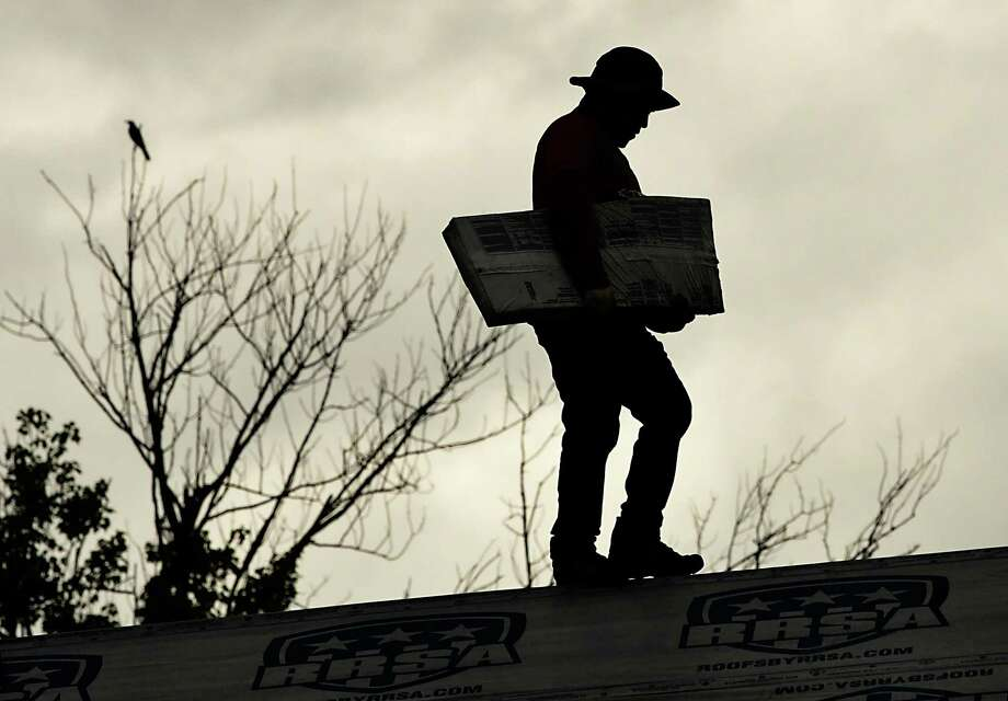 A roofer carries material as he walks along the ridge of a roof of a house on Monday, Aug. 12, 2019 in Colonie, N.Y. (Lori Van Buren/Times Union) Photo: Lori Van Buren, Albany Times Union