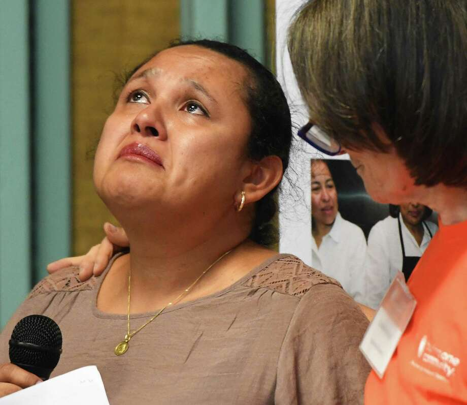 Stamford resident Carla Esquivel, left, sheds a tear while sharing her story of immigrating from Guatemala as Building One Community Executive Director Catalina Horak shows support at the Together We Stand #StamfordWelcomesImmigrants community meeting at Building One Community in Stamford, Conn. Monday, Aug. 12, 2019. In the wake of recent mass shootings in El Paso and Dayton, local immigrants shared their stories in front of representatives from the Stamford Police Department, Stamford Public Schools, City Government and Interfaith Council in a message of unity and support. Photo: Tyler Sizemore / Hearst Connecticut Media / Greenwich Time