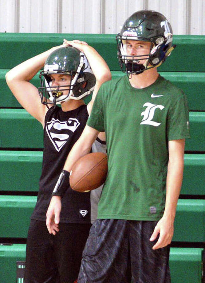 Metro-East Lutheran football players watch the action on Monday during the first official day of practice, which was moved indoors due to the heat and heavy rain on Sunday night.