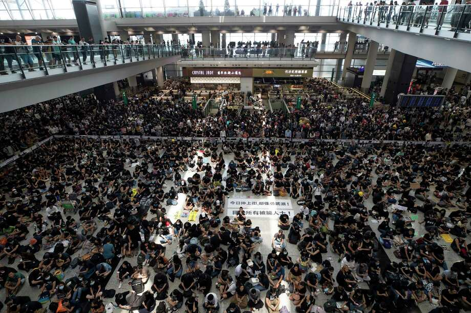 "THIS ADDS TO CLARIFY THE TRANSLATION - Protesters surround banners that read: ""Those on the street today are all warriors!"" center top, and ""Release all the detainees!"" during a sit-in rally at the arrival hall of the Hong Kong International airport in Hong Kong, Monday, Aug. 12, 2019. Hong Kong airport suspends check-in for all remaining flights Monday due to ongoing pro-democracy protest in terminal. (AP Photo/Vincent Thian) Photo: Vincent Thian / Copyright 2018 The Associated Press. All rights reserved"
