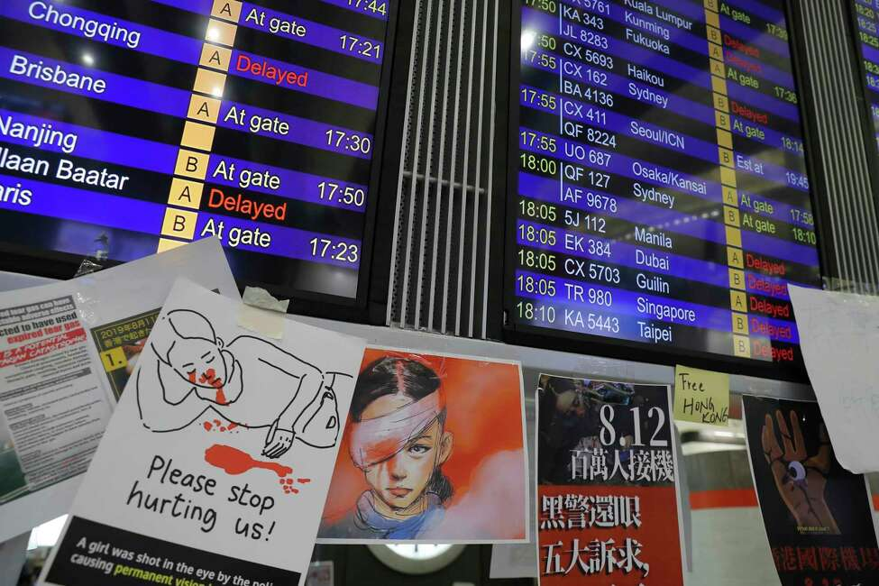 Protest placards are placed around the flights information board as thousands of protesters stage a sit-in protest at the Hong Kong International Airport, Monday, Aug. 12, 2019. One of the world's busiest airports canceled all flights after thousands of Hong Kong pro-democracy protesters crowded into the main terminal Monday afternoon. (AP Photo/Kin Cheung)