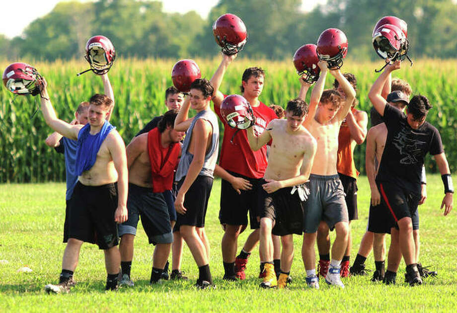 Bunker Hill players break from a huddle after skill position drills for a water break during the first day of practice Monday at Bunker Hill High School. The Minutemen are preparing for their first season of eight-man football. Photo: Greg Shashack / The Telegraph