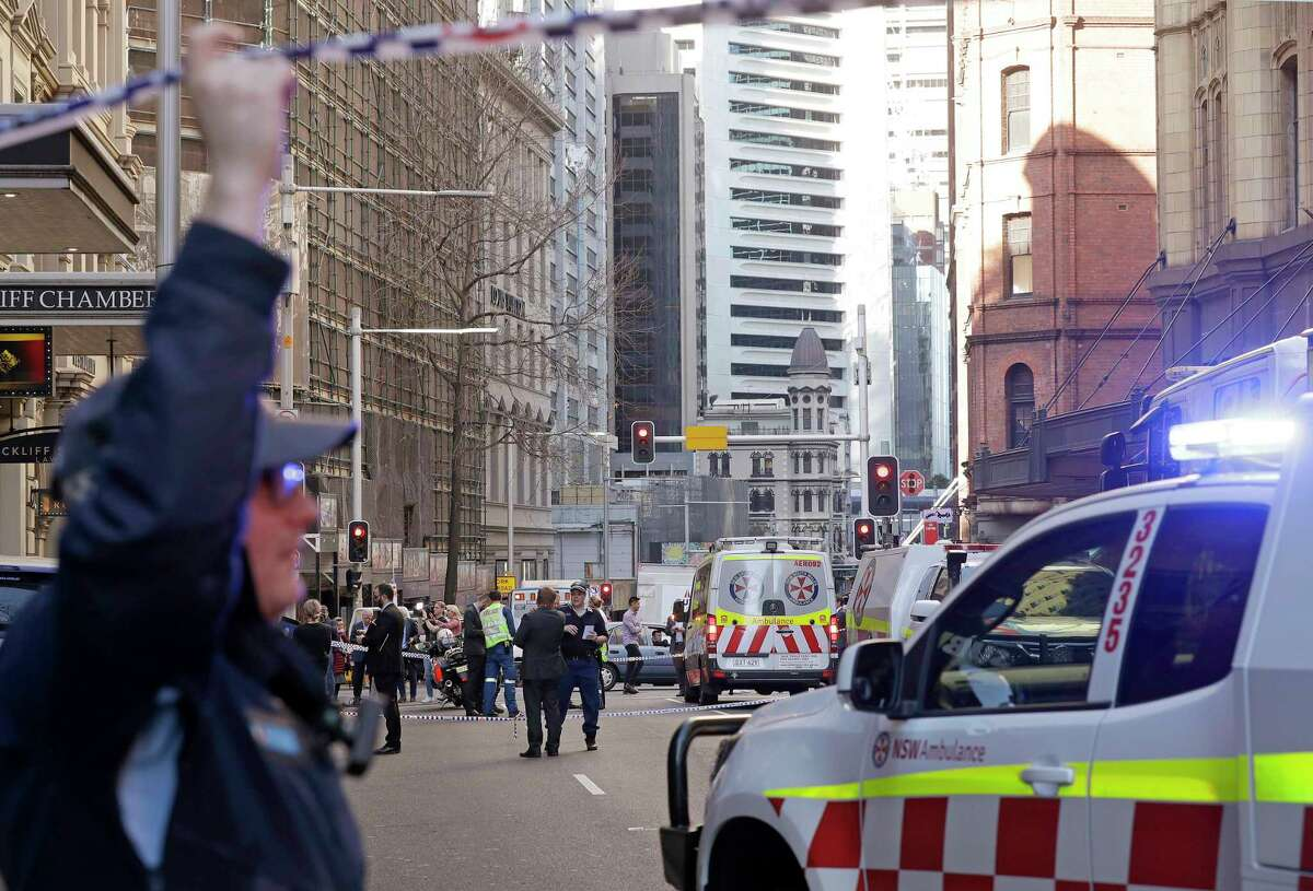 Emergency workers stand at a scene after a man, wielding a long knife, attempted to stab several people in Sydney, Australia, Tuesday, Aug. 13, 2019. Police and witnesses say the knife-wielding man yelling
