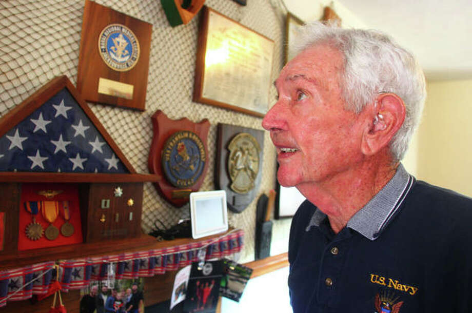 Alvin Marsh looks at one of his photos from his Navy days at his South Jacksonville home Aug. 7. Photo: Rosalind Essig | Journal-Courier