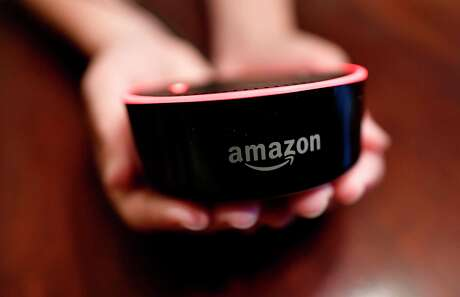 """FILE- In this Aug. 16, 2018, file photo a child holds his Amazon Echo Dot in Kennesaw, Ga. Technology companies are pushing the """"smart home,"""" selling appliances and gadgets that offer internet-connected conveniences you didn't know you needed. (AP Photo/Mike Stewart, File)"""