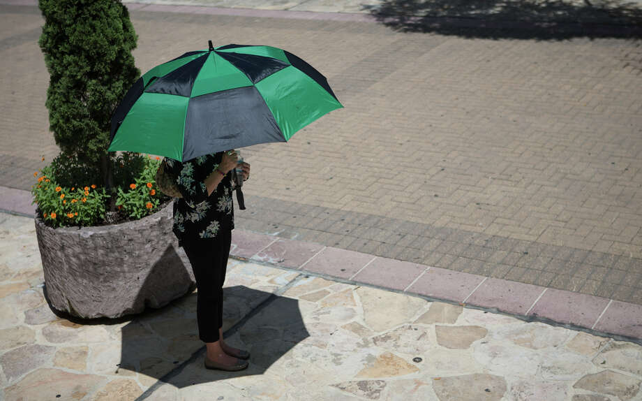 A woman watches from under an umbrella as leaders in the San Antonio community speak during the wake of a heat advisory Monday, August 12, 2019, at the Main Plaza downtown San Antonio. Temperatures are expected to high throughout the week. Photo: Rebecca Slezak, Staff Photographer / © 2019 San Antonio Express-News