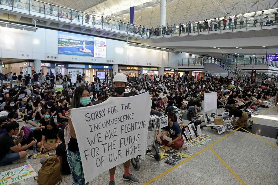 """Demonstrators hold a sign reading """"Sorry For The Convenience We Are Fighting For The Future of Our Home"""" during a protest at the Hong Kong International Airport on Aug. 13, 2019. Photo: Bloomberg Photo By Kyle Lam / Bloomberg"""
