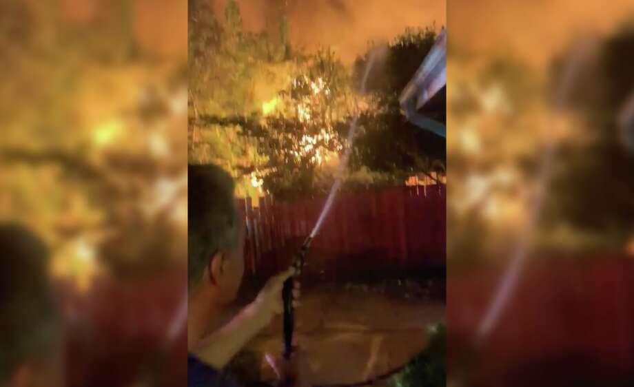 Eliseo Menchaca Sr. sprays his home and property with a garden hose as his neighbor's home erupts in flames along Wimberly Street in north Houston on Monday, Aug. 12, 2019. Photo: Courtesy Eliseo Menchaca Jr. Via OnSceneTV