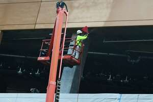 Construction workers with Brookfield Properties paint the garage exterior at the SoNo Collection mall Tuesday, July 30, 2019, in Norwalk, Conn. The 1 million square foot mall plans to open in the fall of this year.