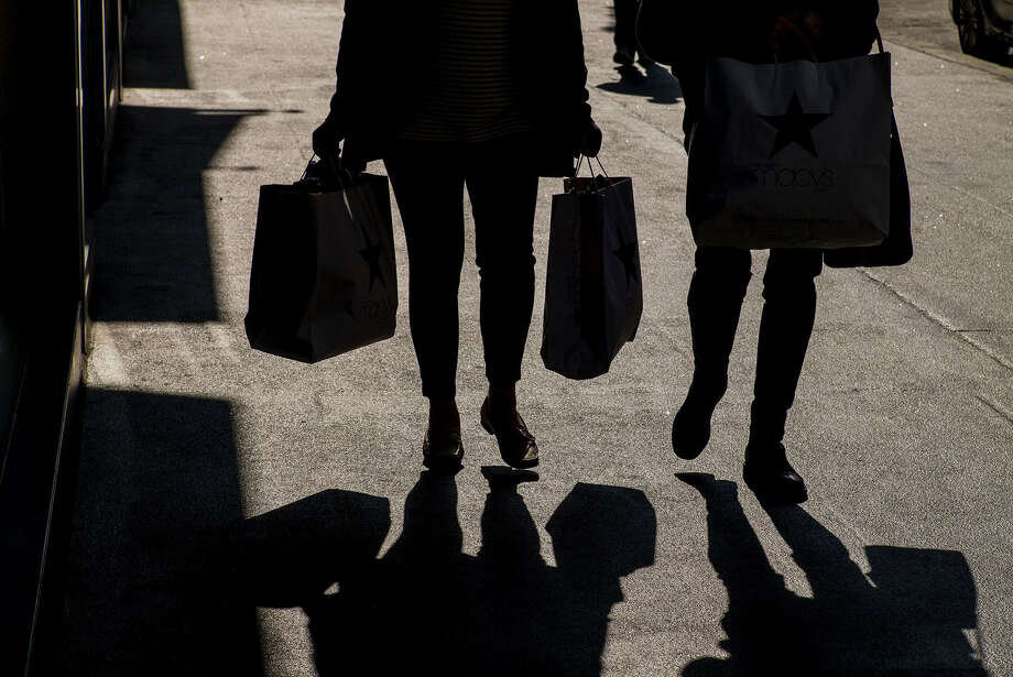 The silhouettes of pedestrians carrying shopping bags in San Francisco on Jan. 22, 2015. Photo: Bloomberg Photo By David Paul Morris. / 2015 Bloomberg Finance LP