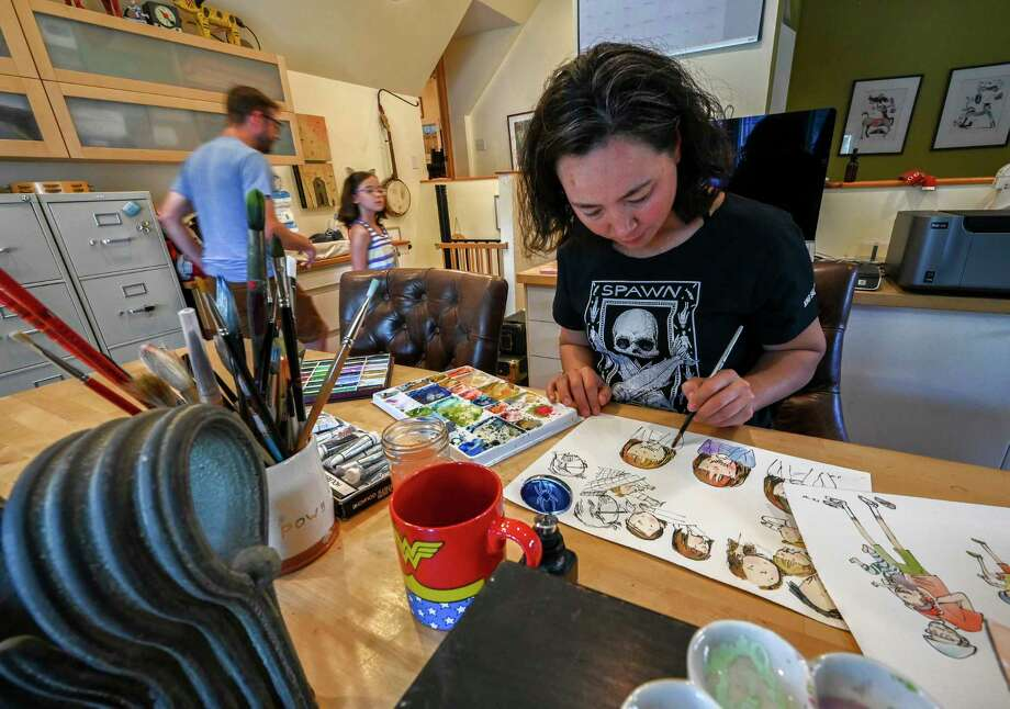 Robbi Behr works on an illustration while her husband, Matthew Swanson, and their daughter spend time at their home in Chesterown, Md. Photo: Washington Post Photo By Bill O'Leary / The Washington Post