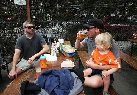 Joe Danyluk of Marin (left), hangs out with Brian Sheehan, 44, and Matthew Sheehan, 2½, both of Kensington, at Westbrae Biergarten in Berkeley. Photo: Yalonda M. James / The Chronicle