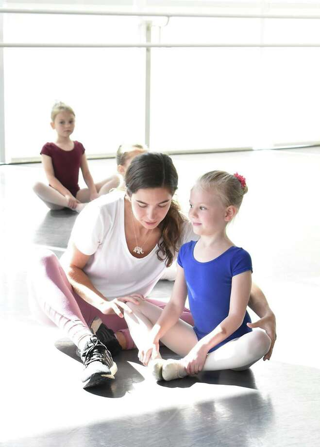 Dance instructor Cassie Sprance helps a young student achieve a desired position. Photo: Contributed Photo