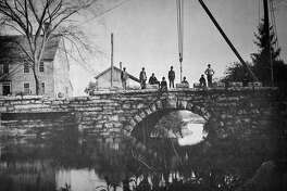The building of Memorial Bridge, 1888-1889, by John Beatty of Leetes Island. The granite blocks that have the names of the first settlers are being set on the north coping with the aid of a hand-operated crane. The building to the left is the Fowler Homestead.