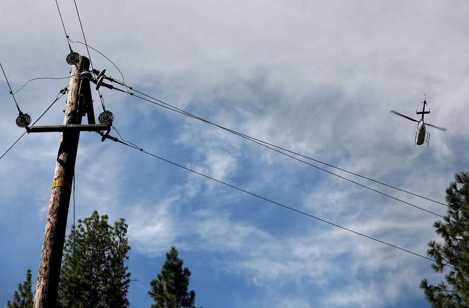 A PG&E helicopter flies 300 feet above inspecting power lines, as PG&E  performs a public safety power shutoff drill around Foresthill, Ca. on Thurs. August 8, 2019, Helicopters and trucks, are used in a trial run for how it will inspect power lines before turning them on after a shut down. Photo: Michael Macor / Special To The Chronicle