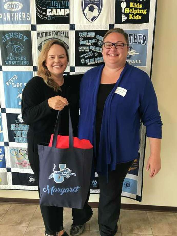 """Jersey County Business Association Director Beth Bear presents a """"Welcome Bag"""" to her sister, Margaret Bear, the new choral director at Jersey Community High School. Jersey County businesses recently provided the bags to 24 new teachers."""