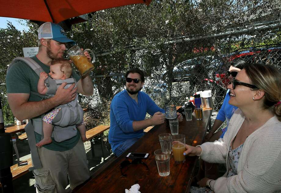 At Berkeley's Westbrae Biergarten, Berkeley residents Shawn Swim (left), 33, drinks beer with daughter Reese, 8 months, on his chest while his wife, Allison (right), looks on with their friends Tom and Anne O'Malley, who are visiting from New Jersey. Photo: Yalonda M. James / The Chronicle