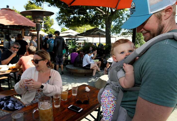 Shawn Swim (right), 33, looks at his daughter Reese, 8 months, as his wife Allison (left), 33, all of Berkeley, converses with visiting friends  at Westbrae Biergarten, located at 1280 Gilman St., in Berkeley, Calif., on Saturday, August 10, 2019.