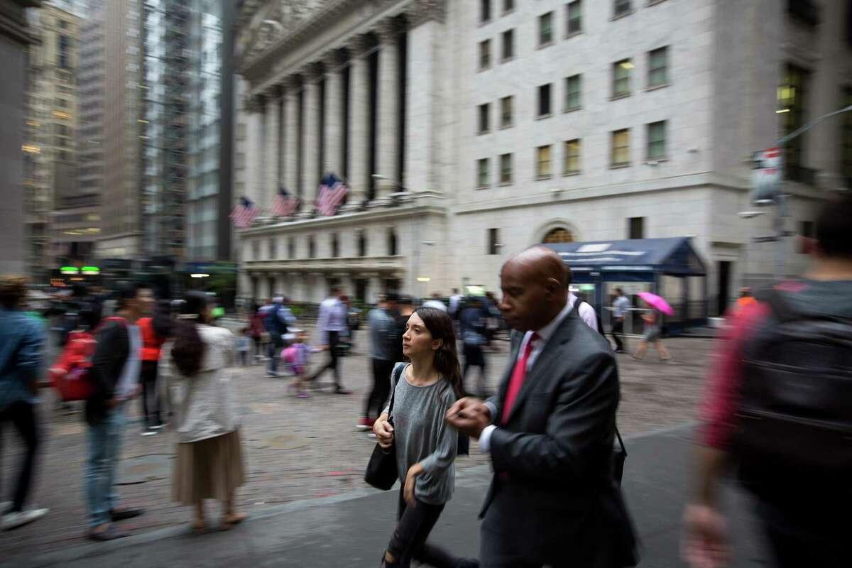 Pedestrians walk along Wall Street near the New York Stock Exchange in New York on Oct. 8, 2018.